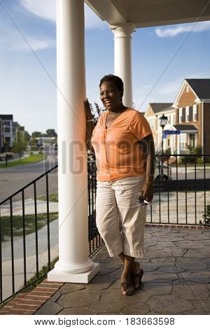 African woman smiling on front stoop of house
