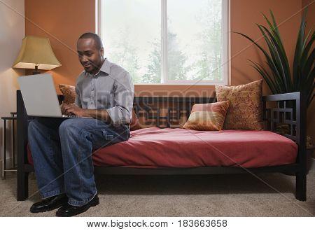 African man using laptop on sofa