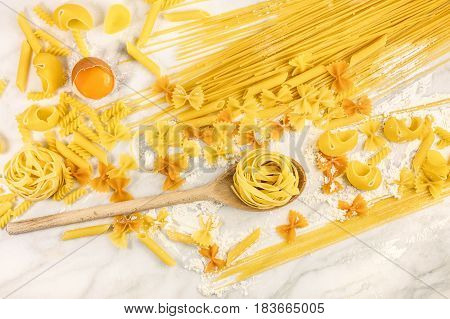 An overhead photo of various types of pasta on a white marble table with flour and an egg, with a wooden ladle and a place for text