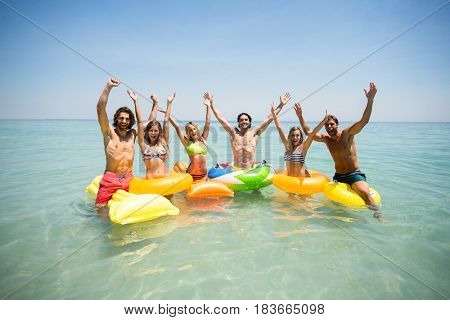 Portrait of cheerful friends enjoying on inflatable rings and pool rafts in sea against sky