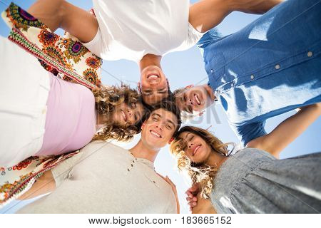 Directly below shot of friends huddling against sky on sunny day