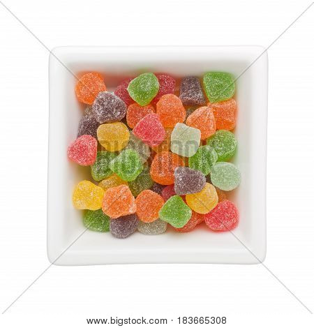 Colorful gummy candies in a square bowl isolated on white background