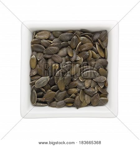 Pumpkin seeds in a square bowl isolated on white background