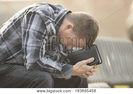 Middle-aged man praying on bench in outdoors