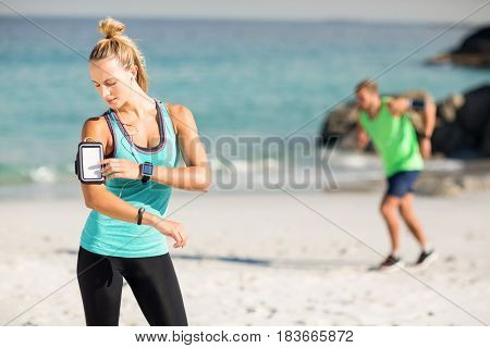 Woman using smartphone on armband while listening music at beach