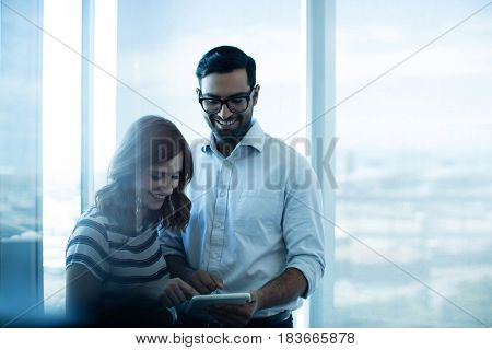 Smiling business couple using digital tablet against glass window in office