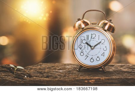Time management concept Copper metal double bell alarm clock on old weathered wooden table background vintage tone of picture.