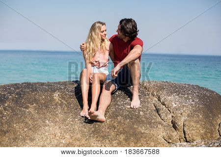 Full length of couple with arm around sitting on rock on shore