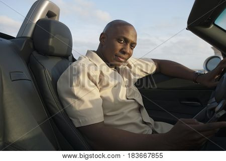 African man sitting in convertible