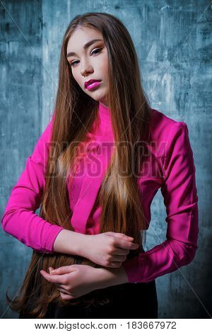 Portrait of a beautiful young woman with long brown hair. Make-up, cosmetics. Hair, healthy hair. Beauty concept.