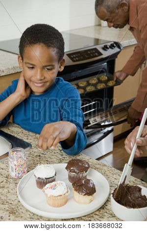 African boy decorating cupcakes