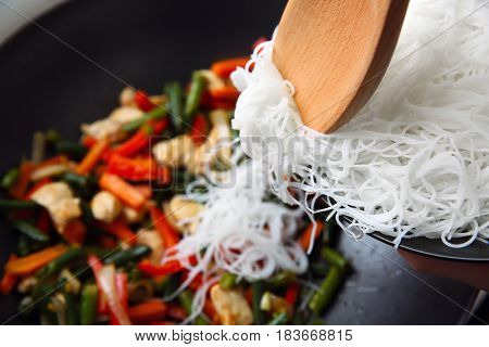Adding delicious rice noodle to vegetables on wok