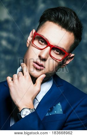 Fashion shot of a handsome young man in elegant classic suit and spectacles. Men's beauty, fashion.