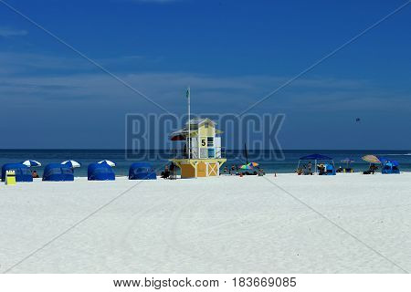 Scene of a sunny day on Clearwater Beach with its white sand beach umbrellas people bathing and sunbathing next to one of the guardhouses that exist all over the beach