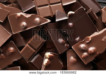 Chopped chocolate bars with nuts as background
