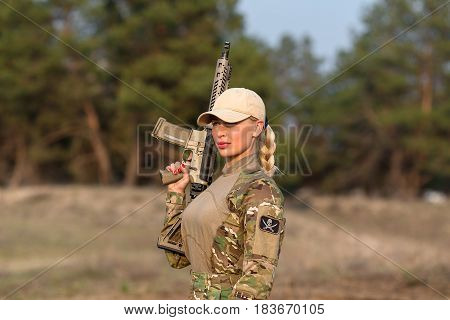 Portrait of beautiful blonde woman ranger in camouflage and with rifle on the forest background