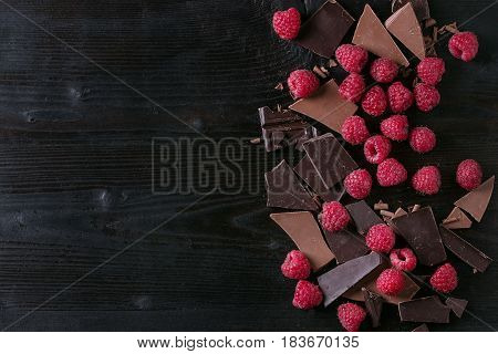 Dark and milk chopping chocolate and chips shavings chopping chocolate with fresh raspberries heap over black burnt wooden background. Top view with space. Chocolate dessert concept