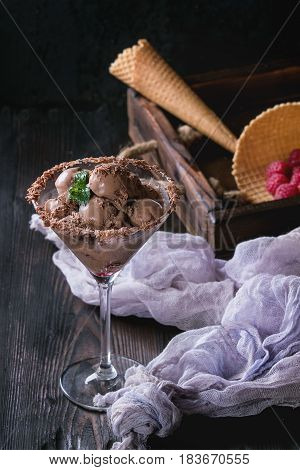 Cocktail glass with chocolate ice cream mini balls with fresh raspberries, mint and waffle cone in wood tray with textile gauze over black burnt wooden background.