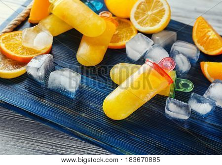 Delicious citrus ice-cream with lemon and oranges on wooden board