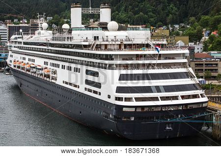 A massive luxury cruise ship docked in a harbor in Alaska