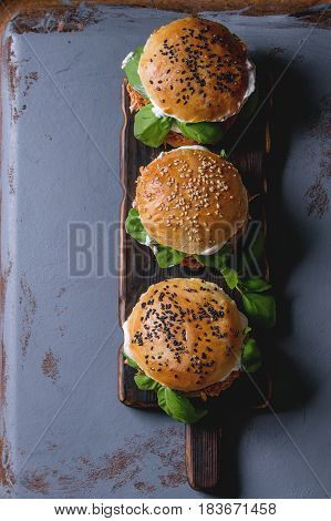 Homemade mini burgers with pulled chicken, basil, mozzarella cheese and yogurt sauce on wooden serving board over gray texture background. Top view with space. Healthy fast food concept