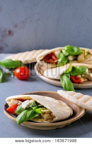Pita bread sandwiches with grilled vegetables paprika, eggplant, tomato, basil and feta cheese served on terracotta plate over gray stone background. Healthy fast food concept.