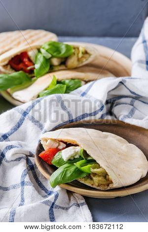 Pita bread sandwiches with grilled vegetables paprika, eggplant, tomato, basil and feta cheese served on terracotta plate over gray stone background. Healthy fast food concept. Close up