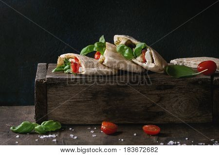Pita bread sandwiches with grilled vegetables paprika, eggplant, tomato, basil and feta cheese on dark wooden box over black background. Healthy fast food concept. Rustic style