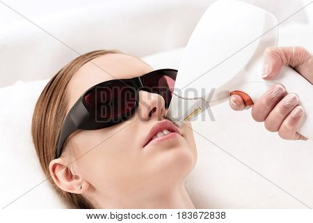 Young Woman Receiving Laser Hair Removal Epilation On Face. Laser Skin Care Concept