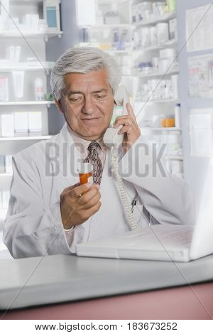Hispanic pharmacists talking on telephone
