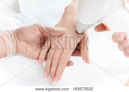 Close-up Partial View Of Woman Receiving Laser Skin Care On Hand