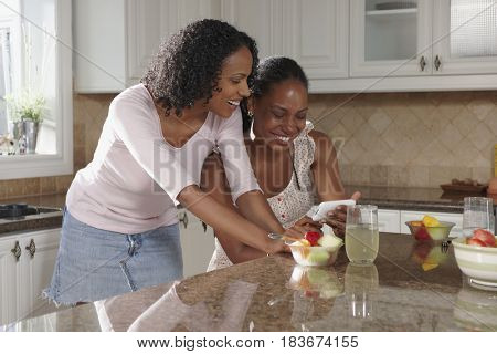 African American sisters in kitchen looking at cell phone