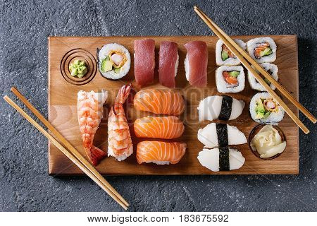 Sushi Set nigiri and sushi rolls on wooden serving board with chopsticks over black stone texture background. Top view with space. Japan menu