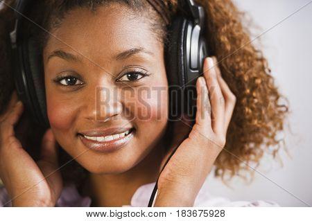 Mixed race woman listening to headphones
