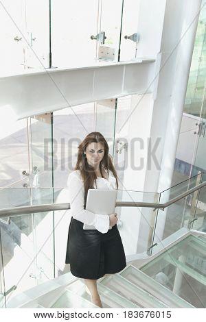 Hispanic businesswoman standing on staircase
