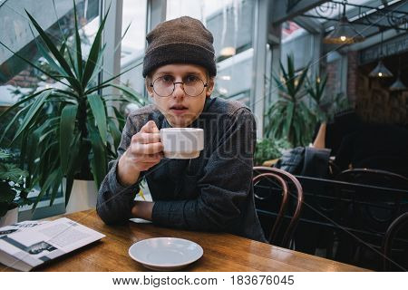 young student with glasses for vision and shirt man drinking coffee in a cafe in free time