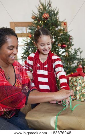 Mixed race mother and daughter wrapping Christmas gifts