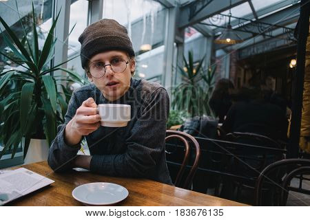 young handsome man in glasses for vision and shirt man drinking coffee in a cafe in free time