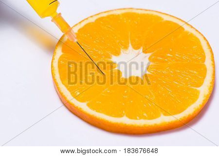Science Experiment With Orange And Syringe Isolated On White.