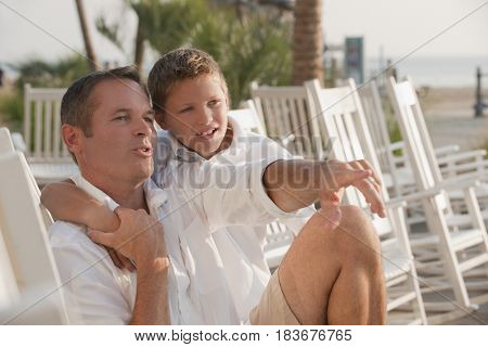 Caucasian father and son sitting in rocking chairs on beach