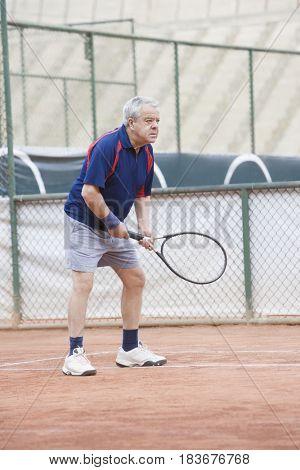 Senior Hispanic man playing tennis