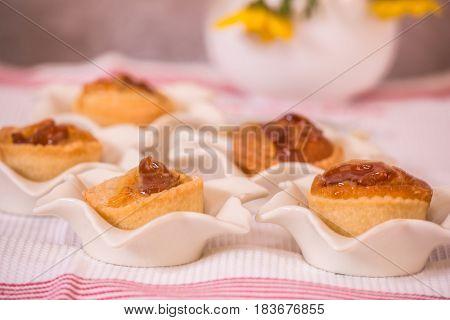 Professional baking. Magnificent portioned tartlet cakes with filling of mousse. Background - white porcelain elegant vases