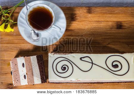 Professional bakery. Three-layer chocolate cake, decorated with chocolate patterns. Background - porcelain cup with hot tea. Holiday cake Three-colate