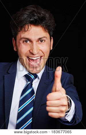 Cheering businessman smiling and holding thumb up