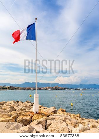 view over the bay with France flag and alpes maritimes from Cap d'Antibes Antibes.