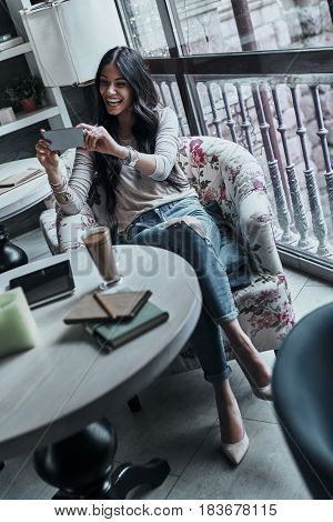Sharing self portraits with her boyfriend. Attractive young smiling woman taking selfie using her smart phone while sitting in restaurant