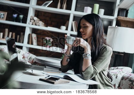 Enjoying coffee at her working place. Thoughtful young woman holding a cup while sitting at her working place
