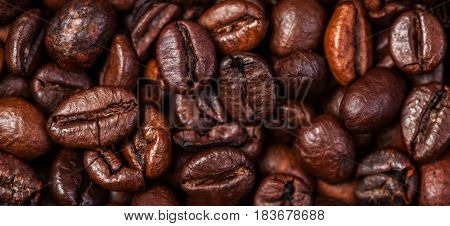 Coffee beans background macro. Dark Roasted coffee beans textured wal lpaper for your design with copy space