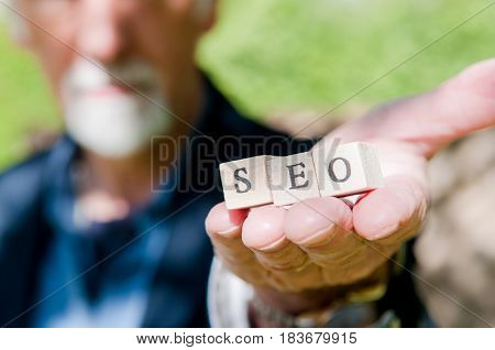 Male Hand Holding Seo Lettering For Website Optimization And Increase Traffic