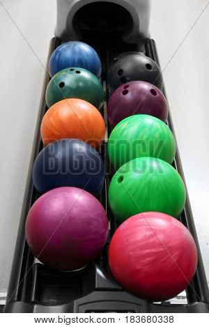 Colorful balls on rack in bowling club